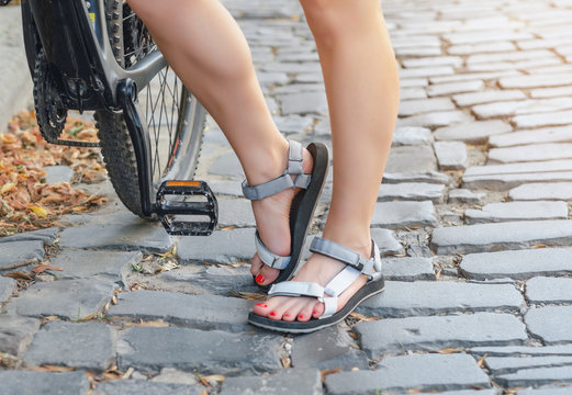 Girl legs in pedicure sandals on old granite pavers with bicycleGirl legs in pedicure sandals on old granite paving slabs with bicycle wheels. Healthy lifestyle, urban, old town