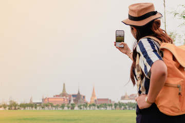 Asian female tourists Take pictures of the grand palace with a smartphone.