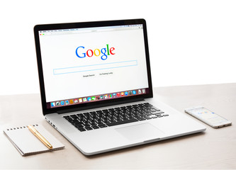 Google webpage on Macbook pro and iPhone display. Google is an American multinational corporation specializing in Internet related services and products
