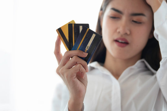 Depresses woman looking at many credit cards scared with a lot of debt.
