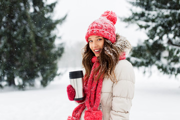 people, season, drinks and christmas concept - happy teenage girl or young woman with hot drink in tumbler outdoors in winter park