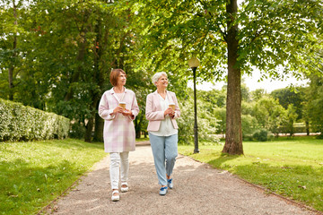old age, retirement and people concept - two senior women or friends drinking coffee walking along...