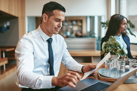 Smiling businessman reading paperwork and using a laptop at work
