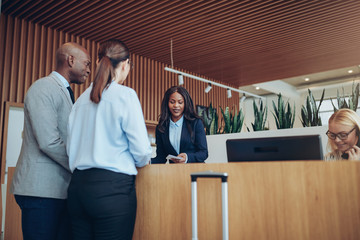 African American concierge checking in two smiling hotel guests