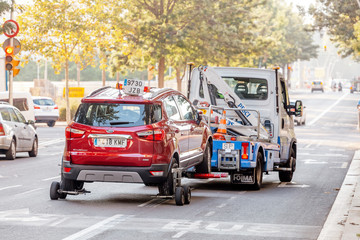 29 JULY 2018, BARCELONA, SPAIN: tow truck transporting car as punishment for wrong parking