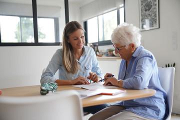 Homehelp assisting elderly woman with paperwork