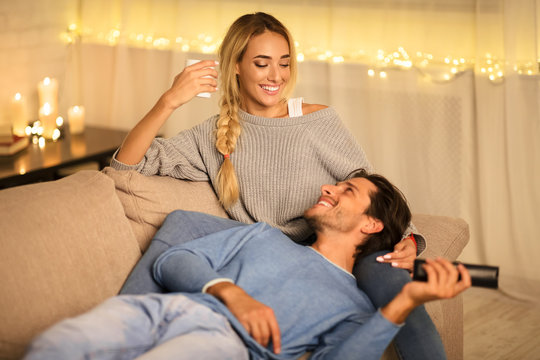Young couple enjoying winter holidays, talking and watching tv
