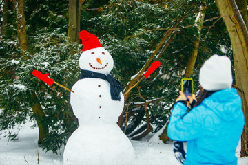 woman taking picture of snowman on phone