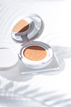 Korean foundation cushion with spf on the water surface under palm leaf shadow. Close up