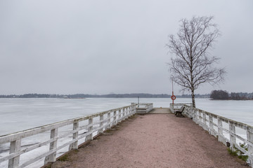 Small pier in Seurasaari island at cloudy, winter day, Finland.