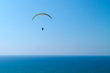 Paraglider in the sky over blue sea