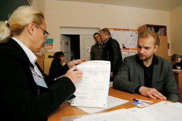 A census enumerator notes details from a resident during a population count in the rebel-controlled city of Donetsk