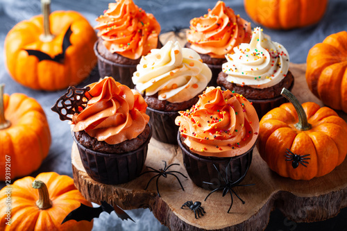 Halloween cupcakes and pumpkins on wooden background. Sweets for holiday party.