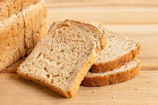 Three slices of whole wheat toast bread isolated on light wood next to a loaf of bread.
