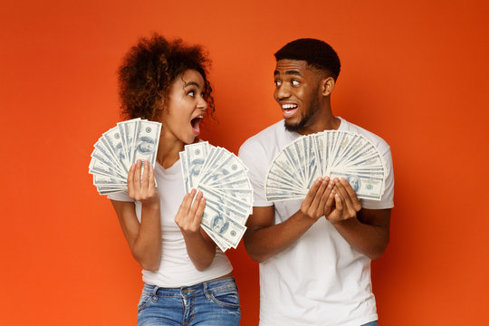 Excited african american couple holding bunch of money banknotes