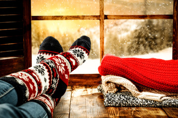 Woman legs with wool socks and window space of winter time