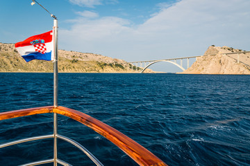 Bridge to the island Krk under blue sky on a sunny summer day. Krk is the big island of the Croatian coast of the Adriatic Sea. Travel landscape. Photo taken from the ship. Croatian flag in left side