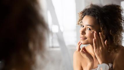 Positive Afro Girl Applying Eye Cream Preventing Wrinkles In Bathroom
