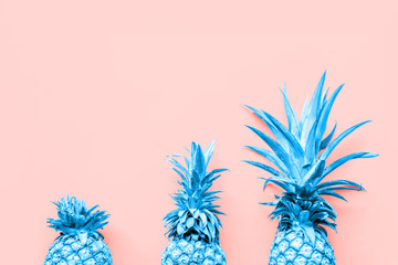 Fotobehang Pop Art Creatively toned pineapples at the coral solid drop with place for text. Trendy modern duotone background. Horizontal