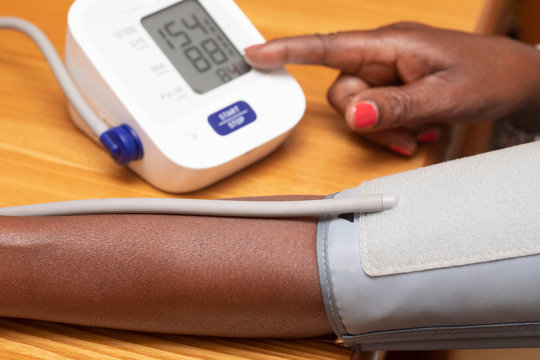 A close up view on the forearm of an African woman as she takes the readings from a blood pressure monitor, the reading falls just above the healthy range, suggesting hypertension.