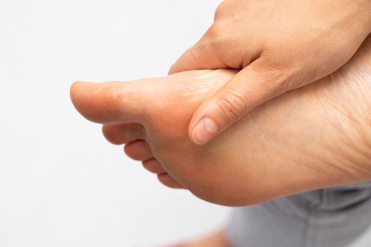 A closeup view on the foot of a person with a busy lifestyle, tired and aching, using hand to rub the underside of the sole and big toe, isolated against a white background.