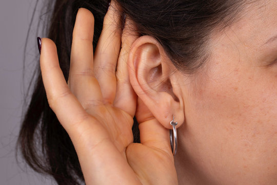 A closeup and side profile view of a young caucasian woman struggling to hear the conversation, gesturing with her hand behind her ear to speak up, wax build up and deafness.