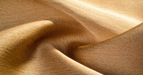 Background, pattern, texture, beige golden silk fabric It has a smooth matte finish and is durable...