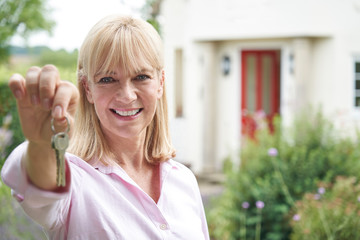 Portrait Of Mature Woman Standing In Garden In Front Of Dream Home In Countryside Holding Keys