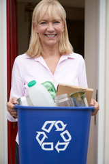 Portrait Of Mature Woman Holding Recycling Bin Of Reusable Waste Outside Front Door