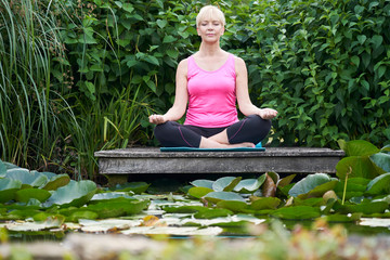 Mature Woman With Eyes Closed In Yoga Position On Wooden Jetty By Lake