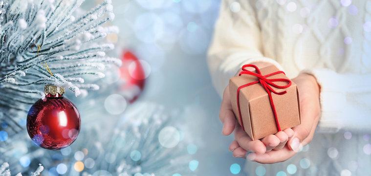 Young woman with gift near Christmas tree, closeup. Bokeh effect