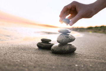 Photo sur Plexiglas Zen pierres a sable Woman stacking dark stones on sand near sea, space for text. Zen concept