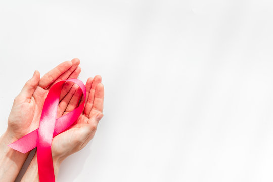 Pink ribbon in hands as symbol of breast cancer awareness on white background top view copy space