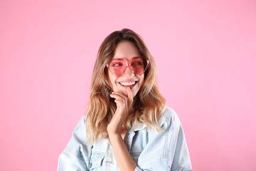 Wall Mural - Young beautiful woman wearing heart shaped glasses on pink background