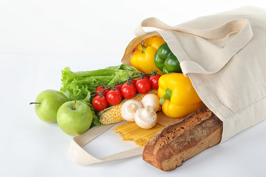 Different fresh vegetables and fruits in tote bag on white background