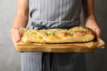 Woman holding tasty homemade garlic bread with cheese and herbs against grey background