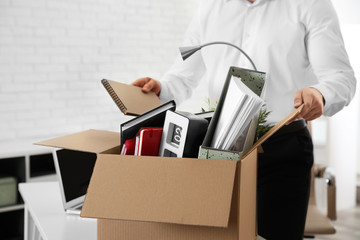 Young man packing stuff in box at office, closeup