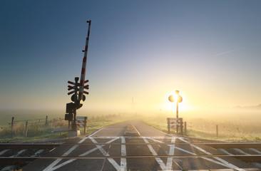 Wall Mural - foggy sunrise over railway crossing on Dutch farmland