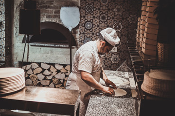 Italian chef in uniform is preparing pastry for pizza at the kitchen.