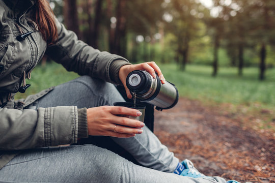 Woman tourist pours hot tea out of thermos in autumn forest. Camping, traveling and sport concept