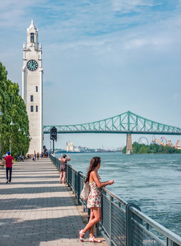 Montreal Old Port harbour woman walking on city street looking at view of St. Lawrence River with Jacques Cartier Bridge and Tour de l'Horloge on summer day. People tourist lifestyle.