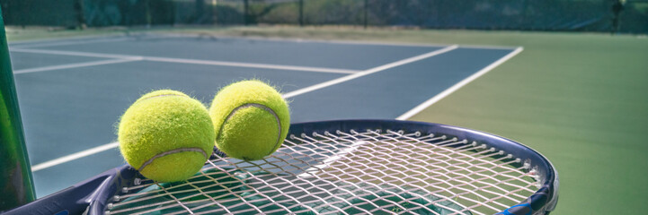 Fototapeta Tennis court panorama background with blue racket and two tennis balls ready to play match on outdoor courts summer sport lifestyle. Mobile photo picture. obraz