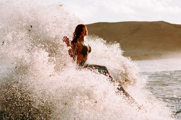 Caucasian redhead woman with mermaid tail perches on rock with pounding waves around her