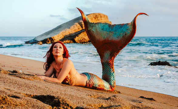 Caucasian redhead woman with mermaid tail reclines on the beach in the waves