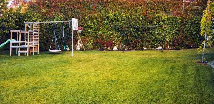 Backyard garden of a house with children playhouse, basketball hoop and soccer goal post