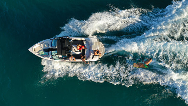 Aerial photo of woman practising waterski in Mediterranean bay with emerald sea at sunset