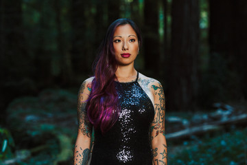 Asian tattooed woman in black evening dress stands in the forest