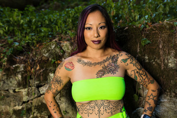 Asian tattooed woman in neon rave clothing poses on an abandoned rock wall in the forest