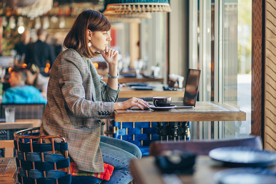 Portrait of a young female freelancer using laptop computer for distance job while sitting in cafe.