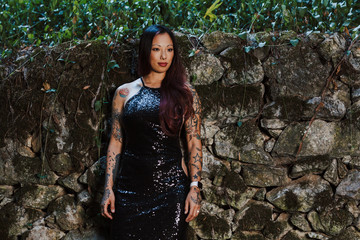 Asian tattooed woman in black evening dress poses on an abandoned rock wall in the forest